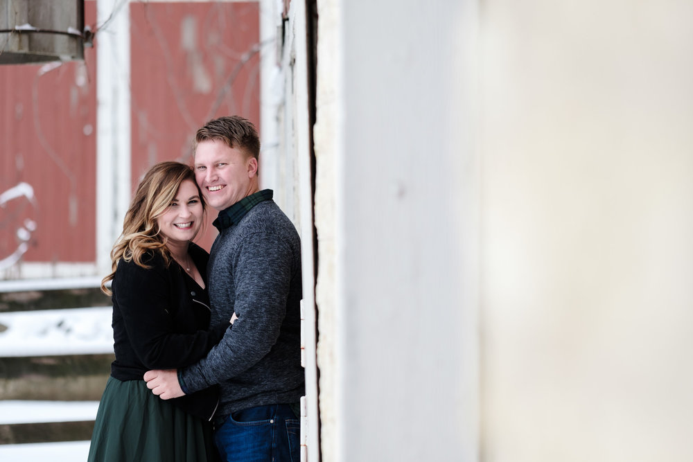 Engagement photo at orchard ridge farms the pavilion, couple leaning against the red barn and laughing