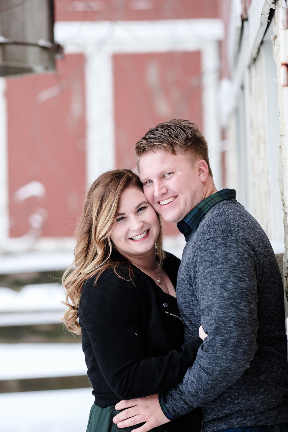 Engagement photo at orchard ridge farms the pavilion, couple leaning against the red barn snuggling to keep warm