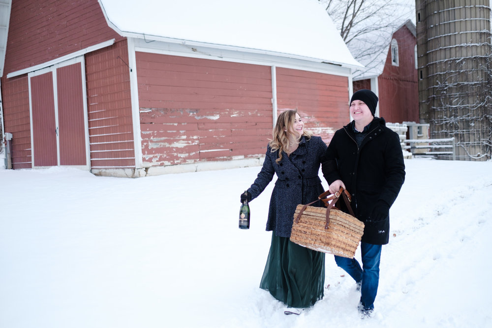Red barn in background at pavilion while couple in black and grey p coats walk with basket laughing and embracing