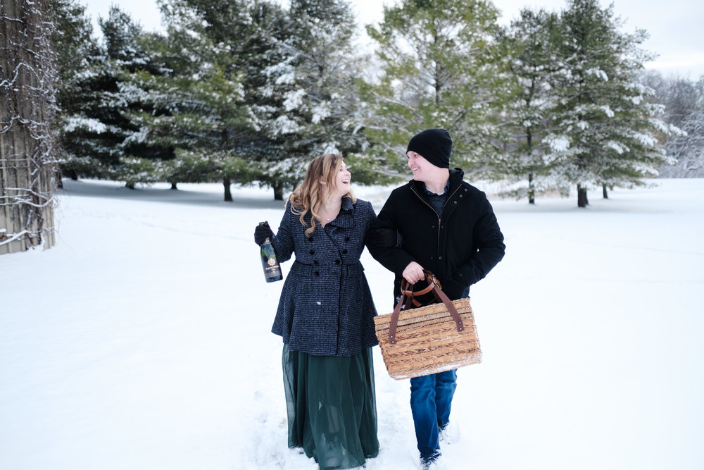 Couple walking from a picnic in the snow with champagne and wicker basket at the pavilion.  photo by rockford wedding photographer b adams photography