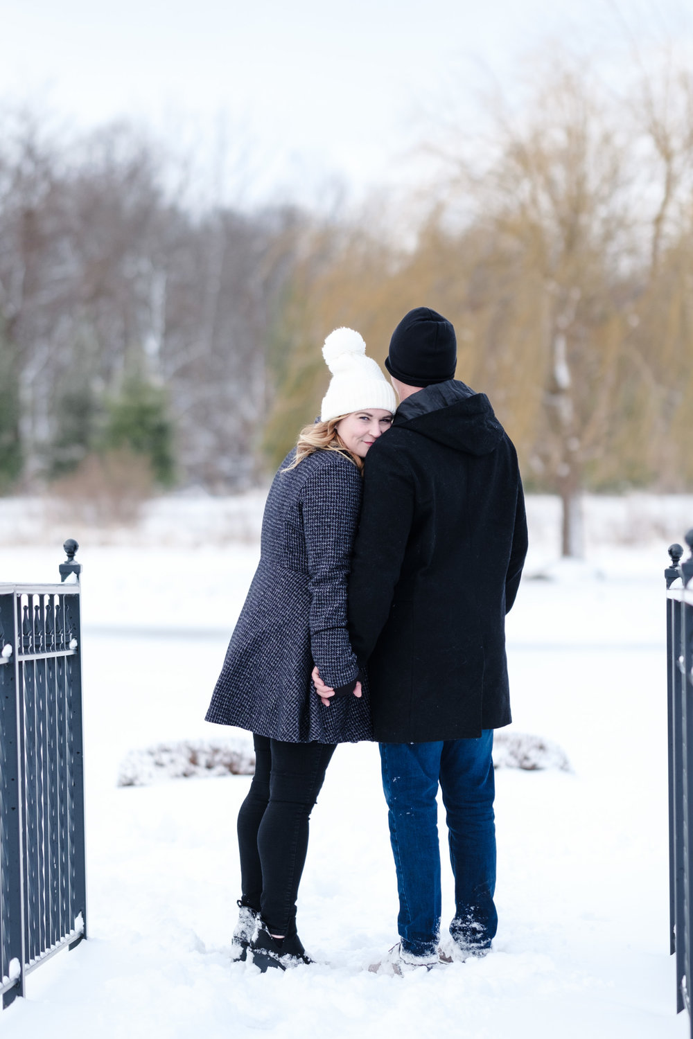 Engagement photo at orchard ridge farms the pavilion, couple embracing overlooking pond with snow covered forest in the distance