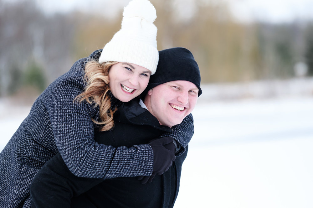 engagement photo at the pavilion at orchard ridge farms with forest and pond in background.  bride grey p coat, groom black p coat with white and black beanies piggy back ride