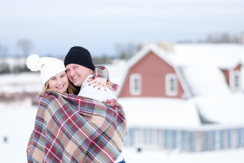 couple wrapped in blanket on bluff overlooking the pavilion during winter wonderland snow engagement session.