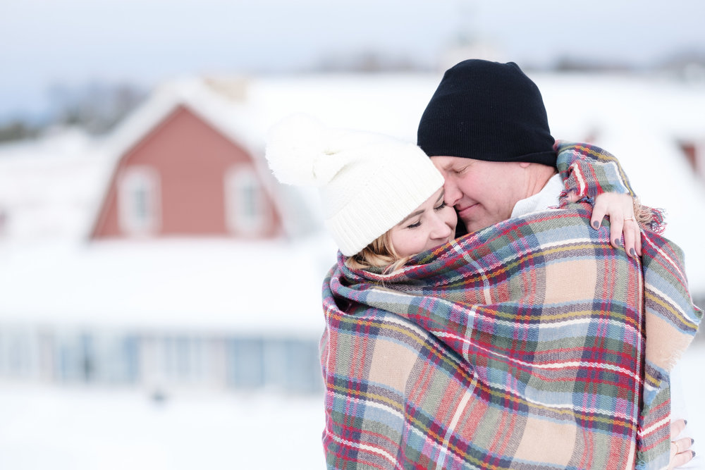 Pavilion in background during engagement session at The pavilion in Rockton Illinois with couple kissing under plaid knit blanket.