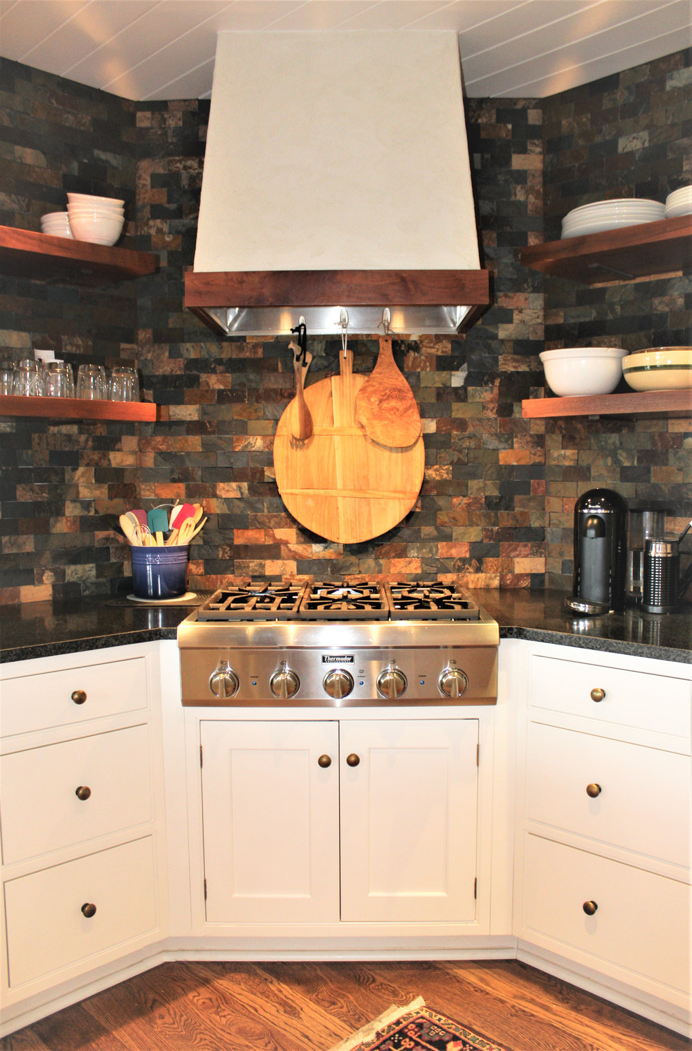 A traditional kitchen blends with the homes log walls. Classic white beaded inset cabinetry, honed black countertops, floating wood shelves that are accented with stacked slate tile add just the right amount of rustic element to the kitchen.
