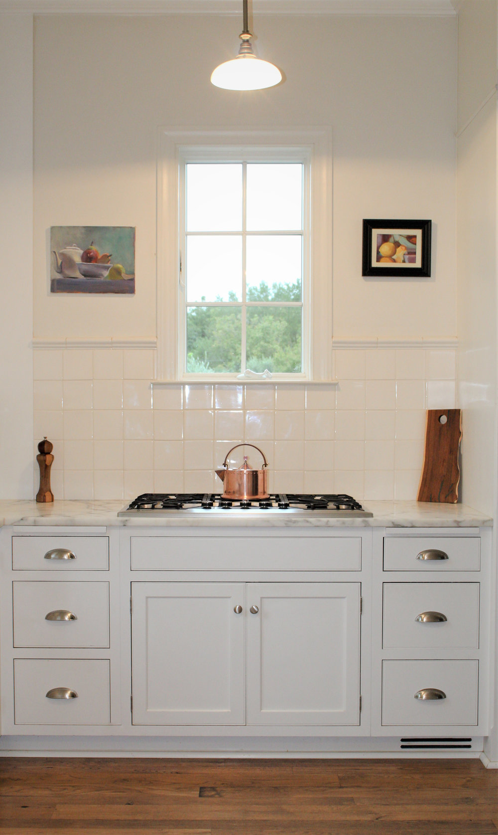A classic white on white kitchen is warmed up with handmade tiles and reclaimed wood floors. Satin Nickel accessories and Calacatta Caldia countertop, give the kitchen a slightly contemporary feel.