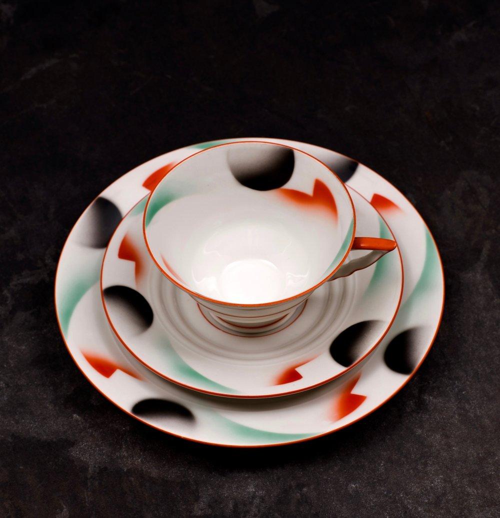 #102 Cup, saucer and plate, Porzellanfabrik Kahla, ca.1930-1932. Green mfr.; Blind cup 34/100. Cup: 5.5 cm H, 10 cm opening, 4.8 cm base Ø. Saucer: 2.2 cm H, 14.8 cm top, 7cm base Ø. Plate: 2.4 cm H, 19.2 cm top, 11 cm base Ø. RM2144