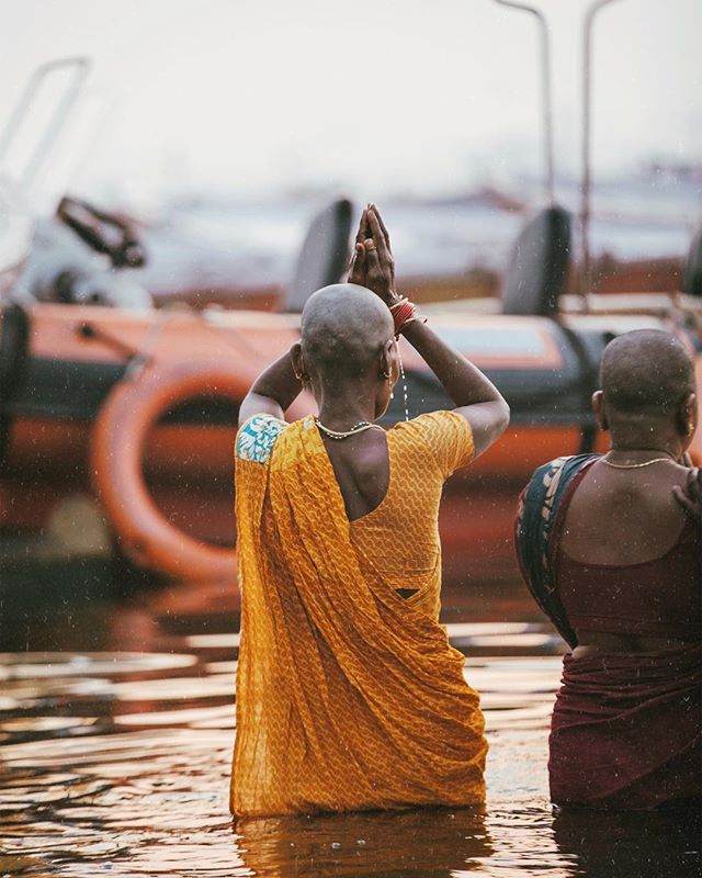 A woman with a newly shaved head sends her morning prayers after a bath in the Ganges River in Varanasi. In these highly spiritual places, Indian men and women often shave their heads as an offering of their hair to the Gods when they are hoping for a certain wish or prayer to be fulfilled. As a result, they typically choose to do so when a loved one is sick, or when a loved one has just passed away. // #varanasi #india #thisisindia #sunrise #visitindia #travelphotography #travel #sunriseporn #incredibleindia #makeportraits #ganges #gangesriver