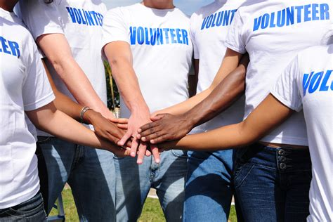 Image of people holding hands in a circle wearing t-shirts with text that reads volunteer.jpg