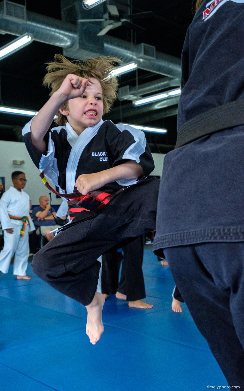 Child karate student kicking bag