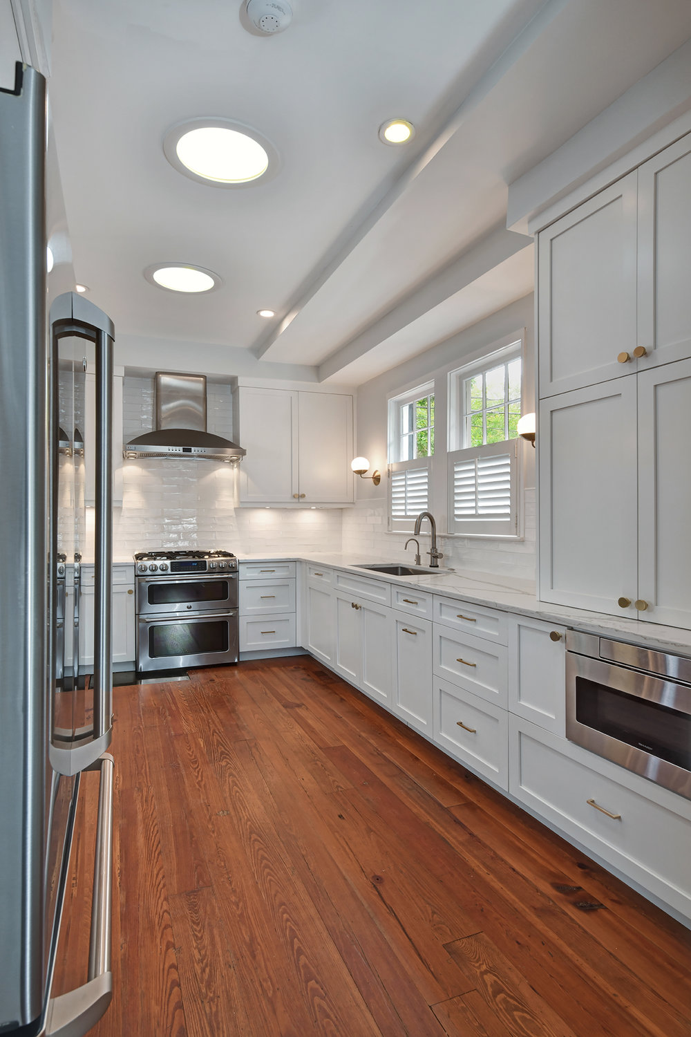 Everything has its place in this upgraded kitchen with ample storage space. Cooper-hued hardware adds a warm touch to the clean white cabinetry.