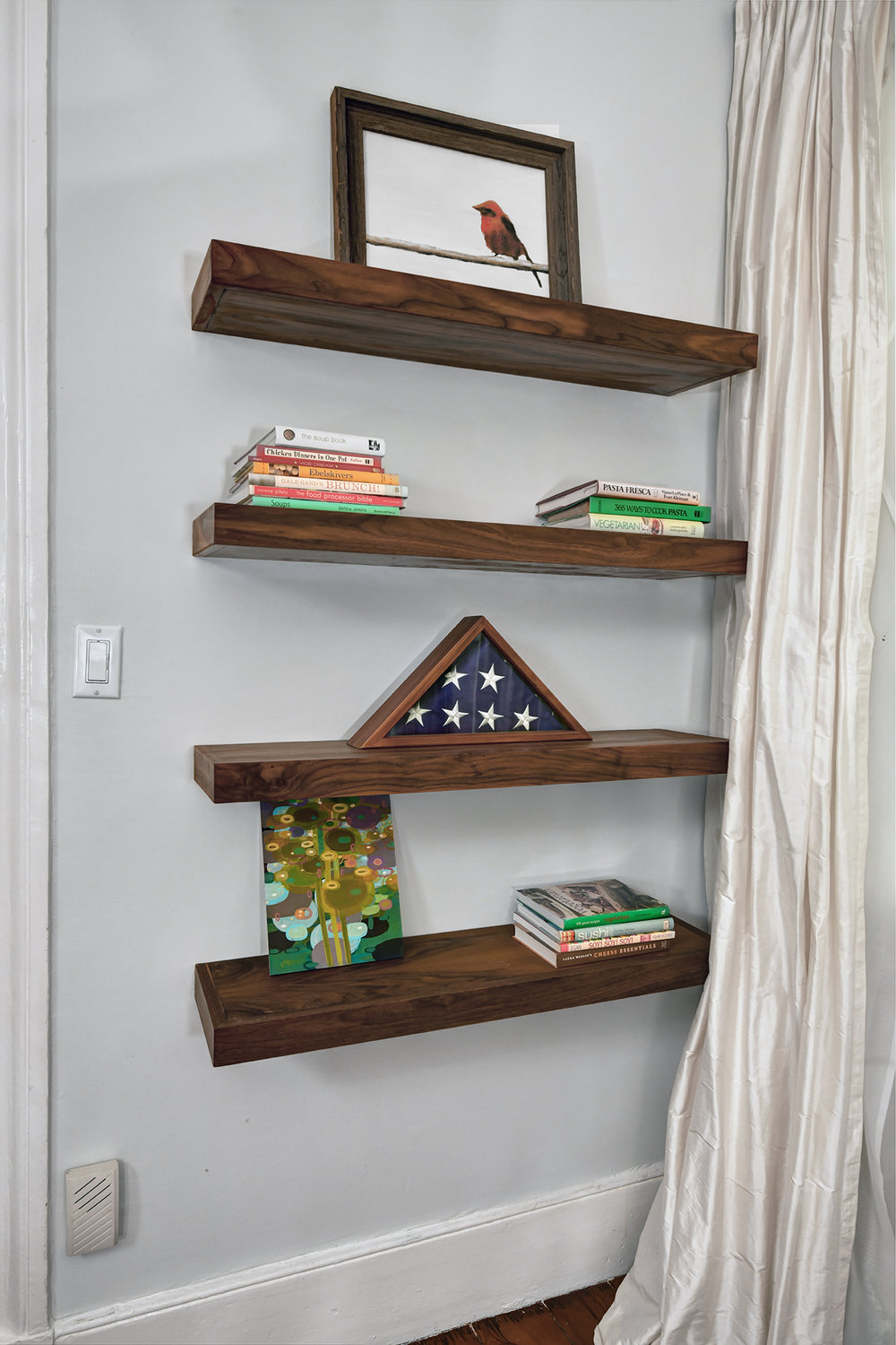 Floating shelves in rich walnut add depth and interest to an interior wall.
