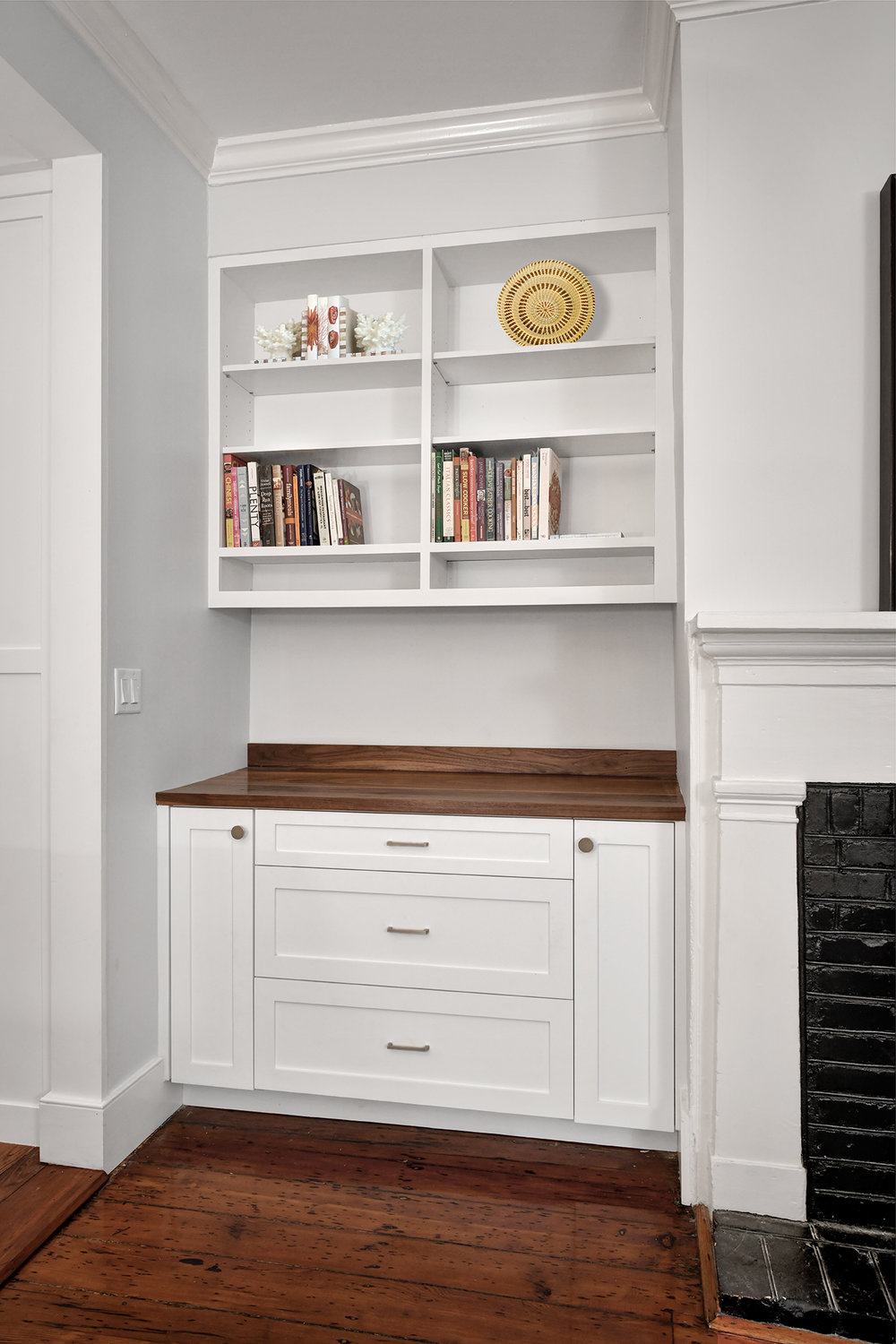 Built-in custom cabinets and shelves make the most of a small area adjacent to the fireplace.
