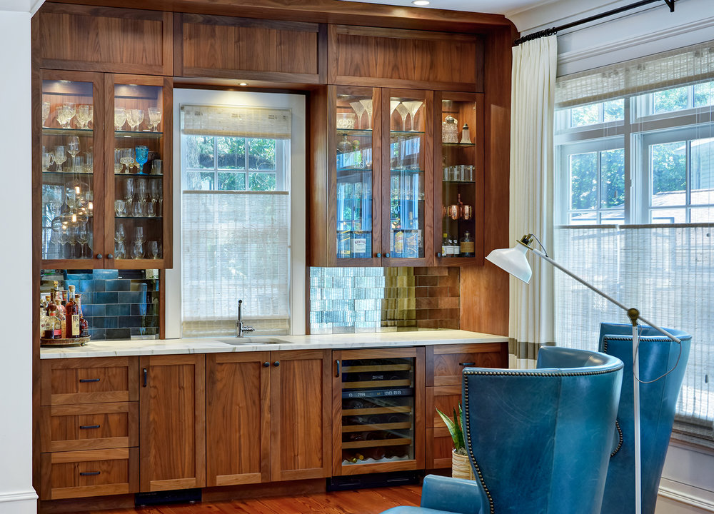 A unique custom bar reflects the individual style of the owners and anchors the room with a beautifully grained walnut wood.