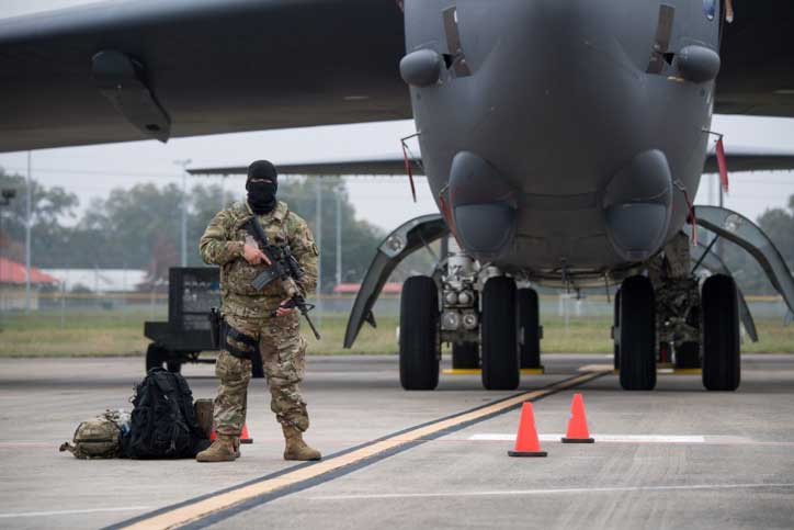 Guarding nuclear weapons in flak jackets (body armor) while holding M16s with 240 rounds of ammunition each.