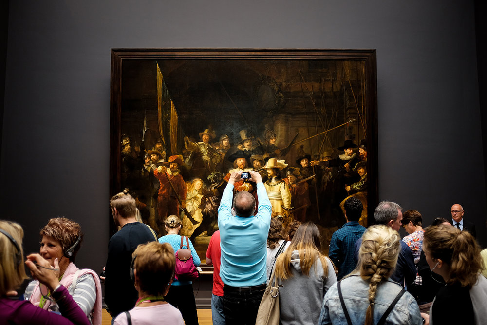 "A visitor to the Rijksmuseum  in Amsterdam, the Netherlands, strains to take a photo of Rembrandt's ""The Night Watch""  on Tuesday, Aug. 25, 2015."