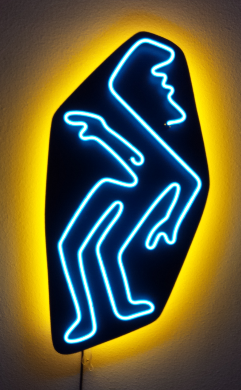 "CHAZ.  Approximately 35"" x 17.5"", sky blue light on black board with yellow backlight (as displayed on a white wall)."