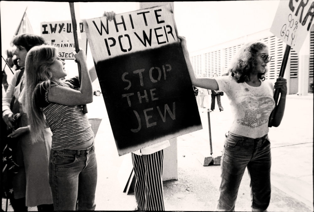 Counter Rally 1977  - Across town, Phyllis Schlafly, gathered almost 15,000 at a counter-conference in which they vowed to uphold traditional pro-family values, using fear of change in a message that resonated with conservatives. Outside and inside the Astrohall, women, young and old, carried signs with racist, anti-Semitic, and hate-filled slogans.  Photo© Janice Rubin