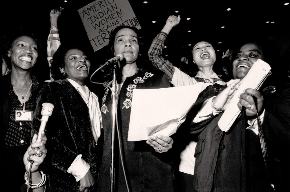 """Coretta Scott King reads a resolution that addresses the needs of minority women. Maxine Waters, who spent three days and nights together crafting the document with hundreds of other women said that when the resolution was read """"Everyone joined in singing 'We Shall Overcome' and women were crying and hugging each other. """"  Photo © Janice Rubin"""