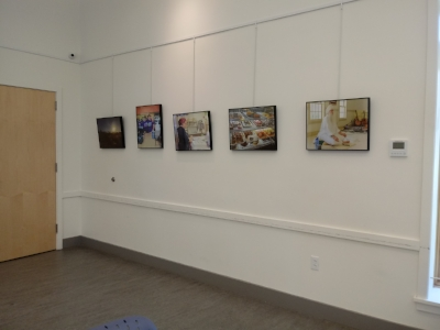 Framed photographs on the wall, befoe straightening.