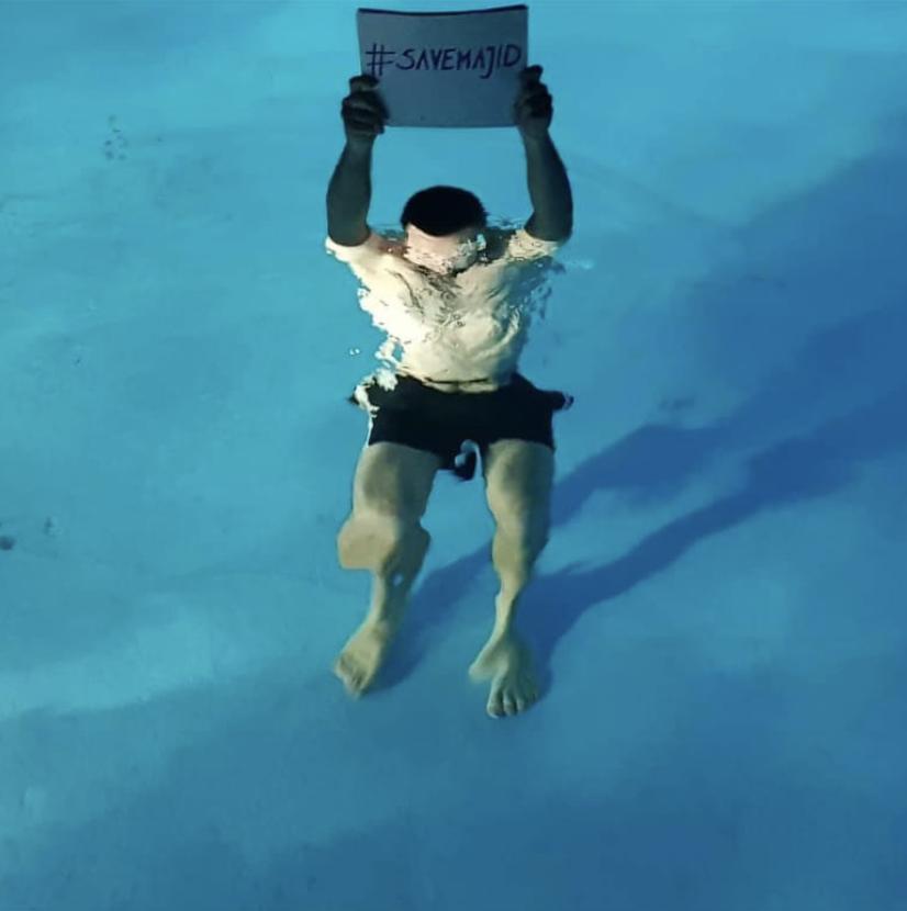 Jakob steht im Wasser und hält ein Schild hoch