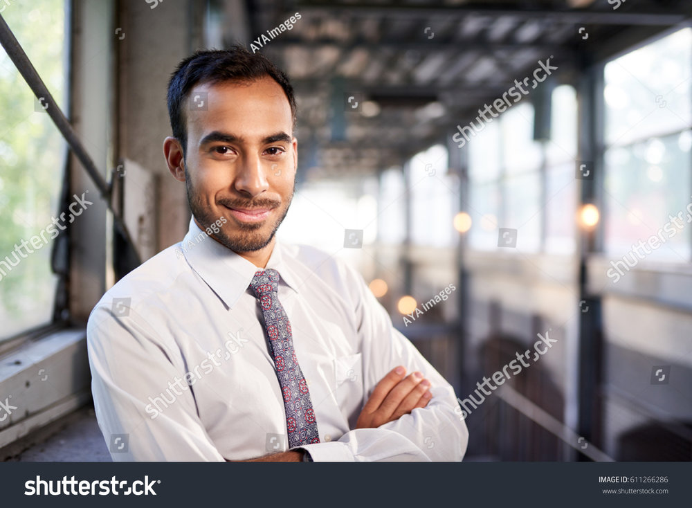 stock-photo-indian-businessman-smiling-confidently-with-cityscape-background-611266286.jpg