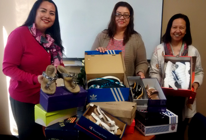 HCA staff shown sorting shoes at HCAD, are From left: Alejandra Gutierrez, Esther Aranda and Roma Estrada from HHSA's Health Care Coverage Access are shown sorting footwear donated for clients of the Third Avenue Charitable Organization.