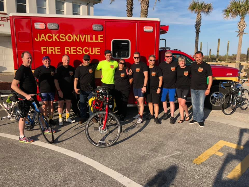 Cal fire/san diego county Fire apparatus engineer Thomas pitman in neon yellow shirt poses with Jacksonville beach firefighters at the end of his memorial bike ride.