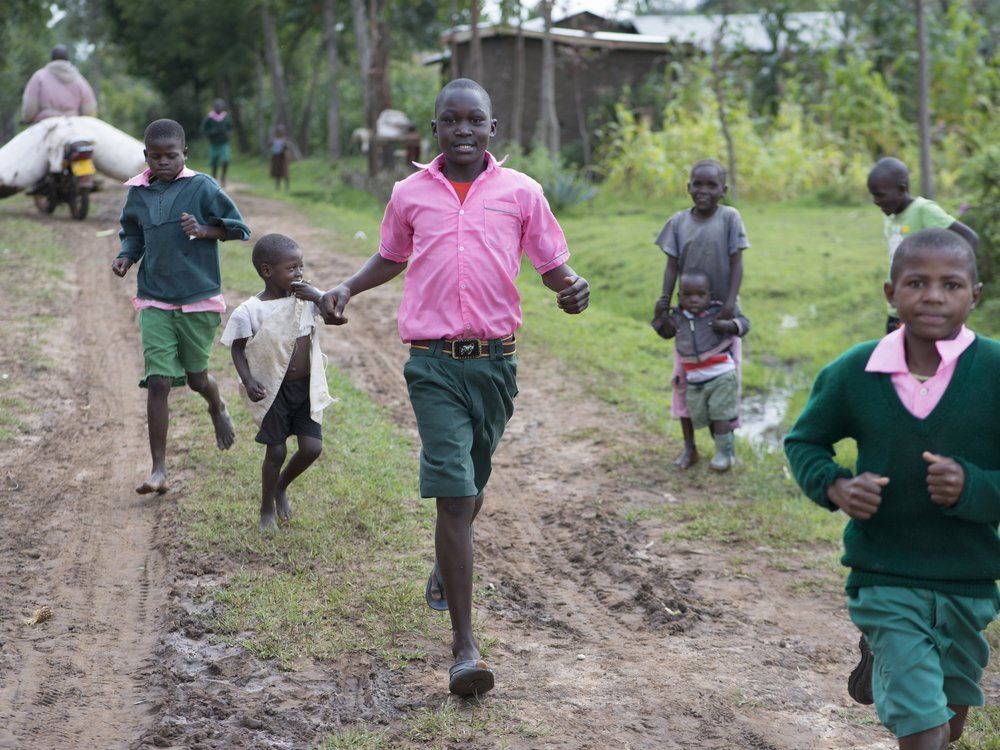 Children running along a road in Kenya