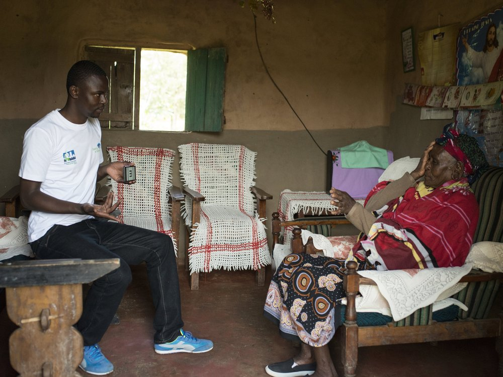 A health worker using the Peek app to check the vision of a lady in her home in Kenya
