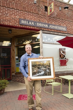 """Jeremy Scarborough with his winning photograph """"Dreaming Fall"""", in front of BTB Coffee Bar"""