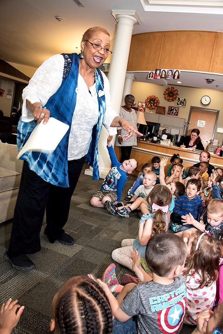 """Photograph of Walthour surrounded by students as she recites her poem """"Shout Sister Lizzie"""" from  SOMDNews.com"""