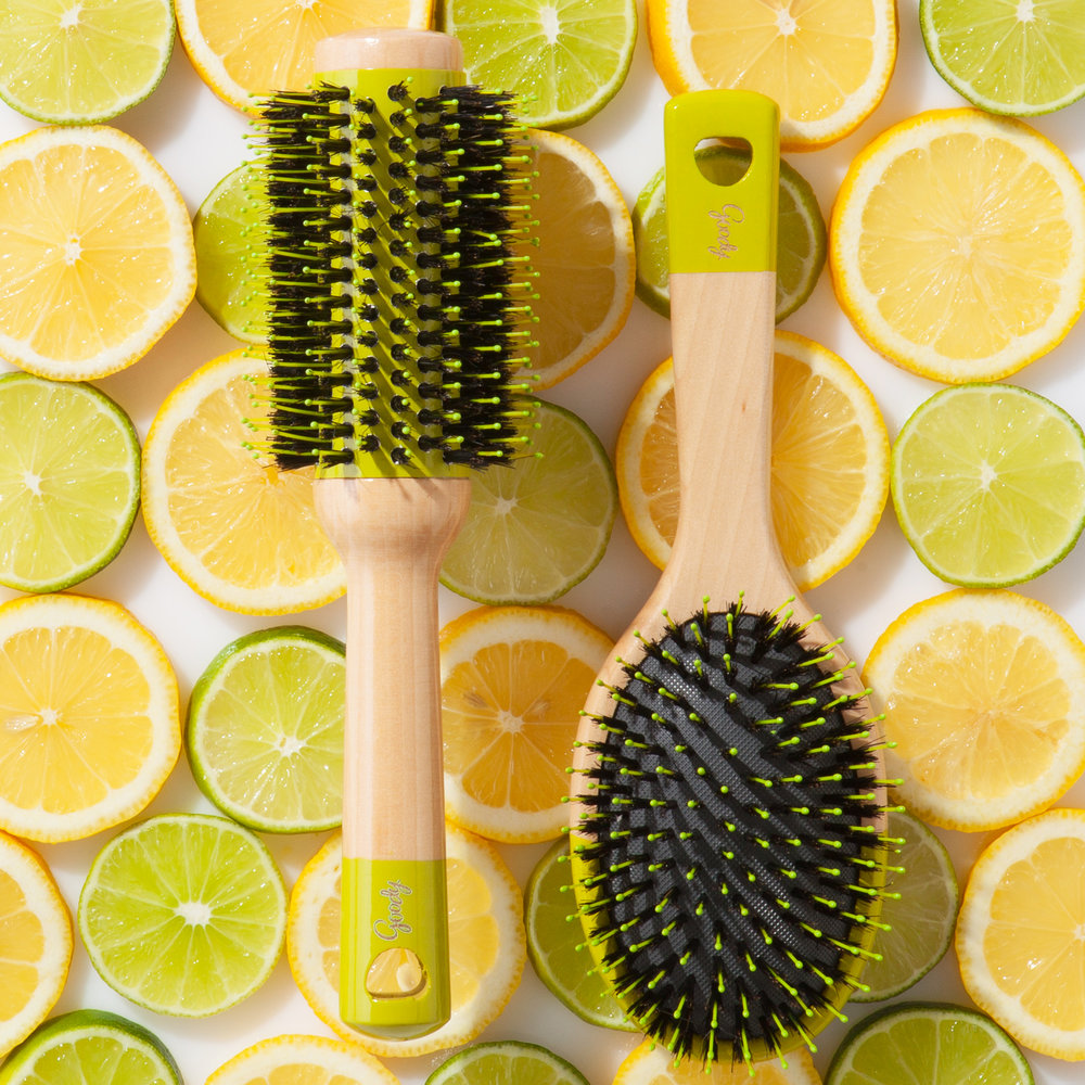Cushion and Round Wood Brushes on top of a bed of sliced lemons and limes