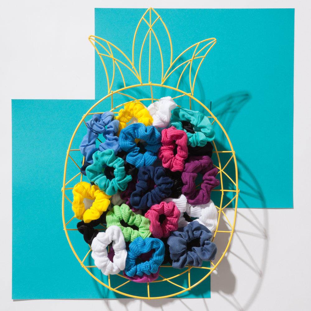 Scrunchies in a wire frame pineapple bowl on blue background