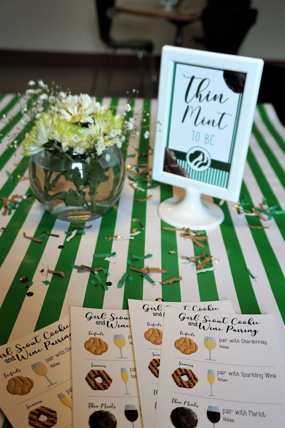Girl Scout cookie and wine tasting tables with daisy floral arrangements, confetti, and sings.