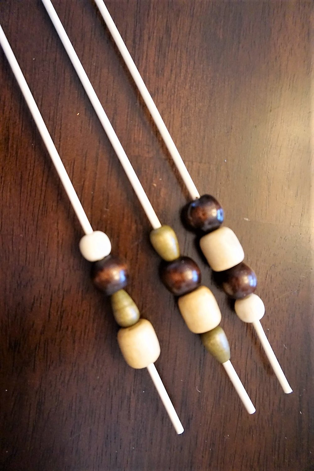 Add wooden beads to skewers to start your own boho arrow decorations.