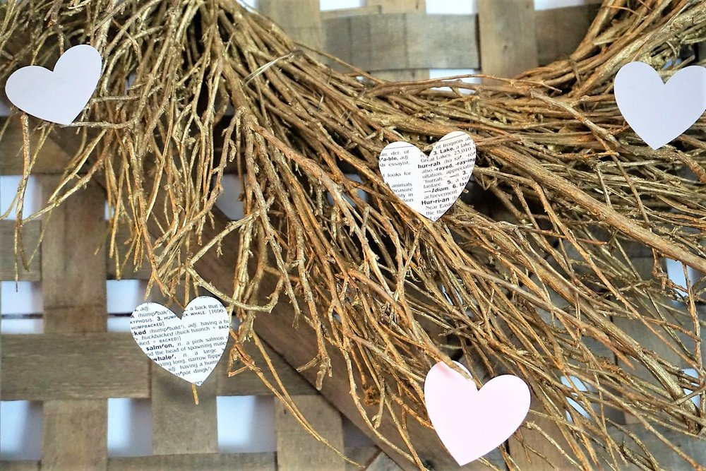 Cut hearts from cardstock and dictionary paper to add to a store bought wreath.