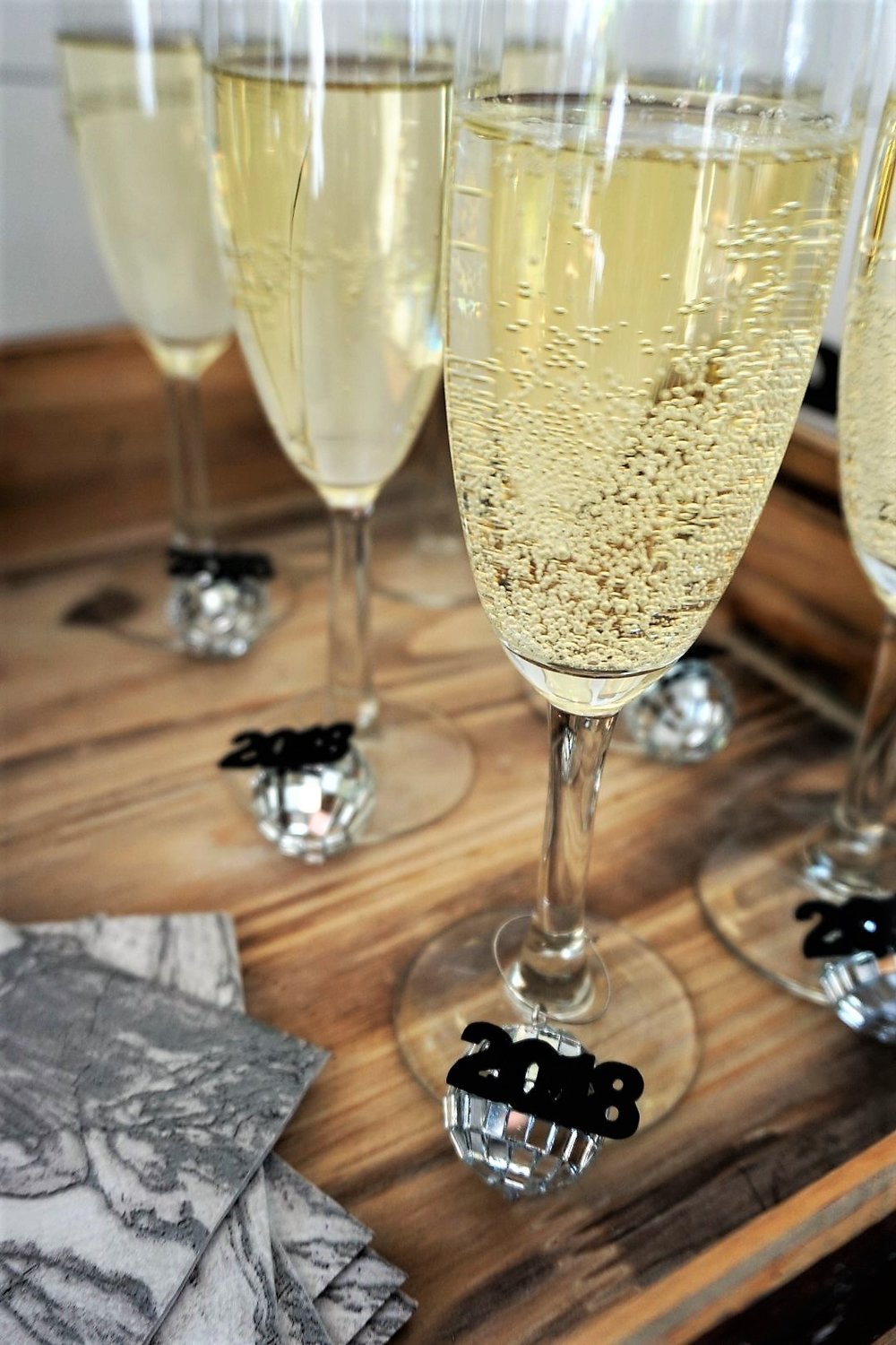 Champagne flutes with DIY New Year's Eve wine charms!