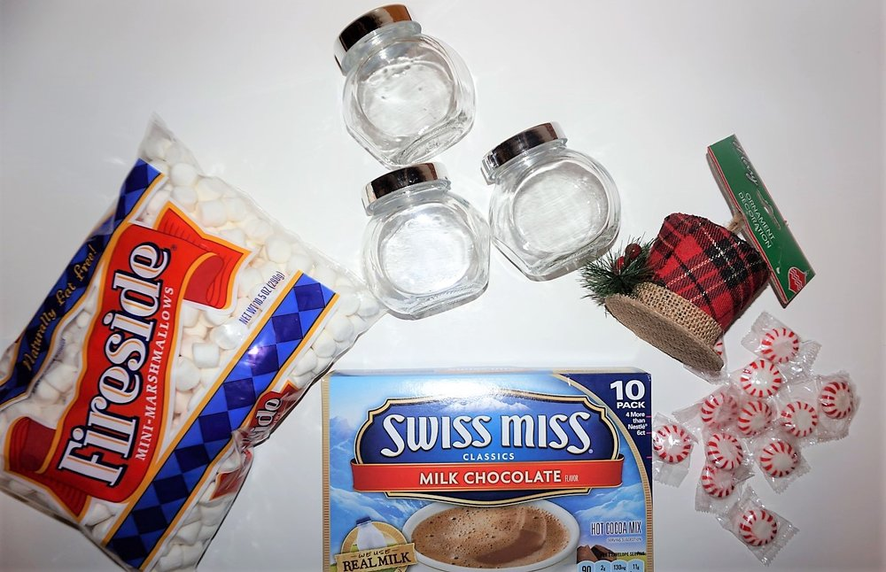 Supplies for a DIY Snowman Cocoa Kit include marshmallows, cocoa packets, glass jars, a hat ornament, and peppermint.
