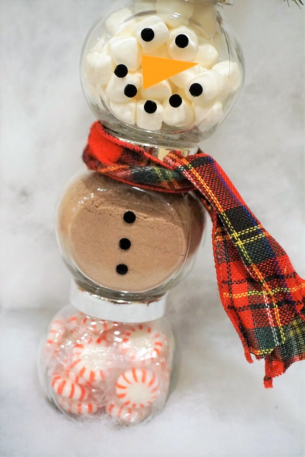Make glass jars into a Snowman Cocoa Kit by cutting out a vinyl face and buttons by hand or using a Cricut.