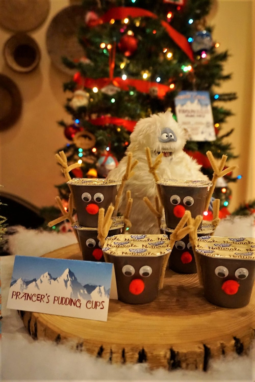 DIY reindeer pudding cups made with pipe cleaners, googly eyes, and felt pom poms.