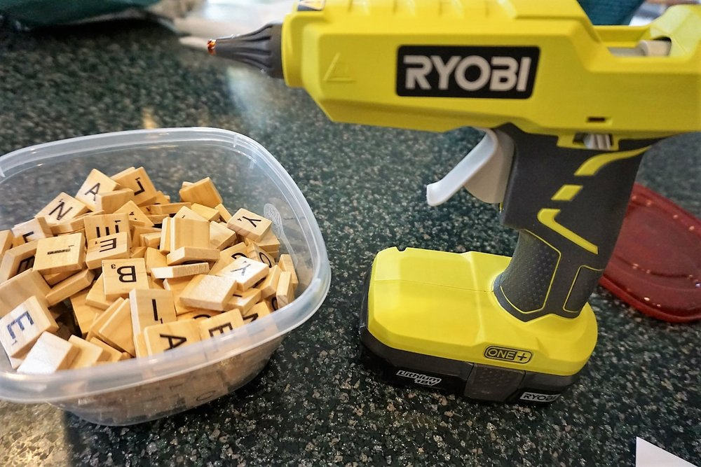 Scrabble tiles and a Ryobi glue gun are staple craft supplies.