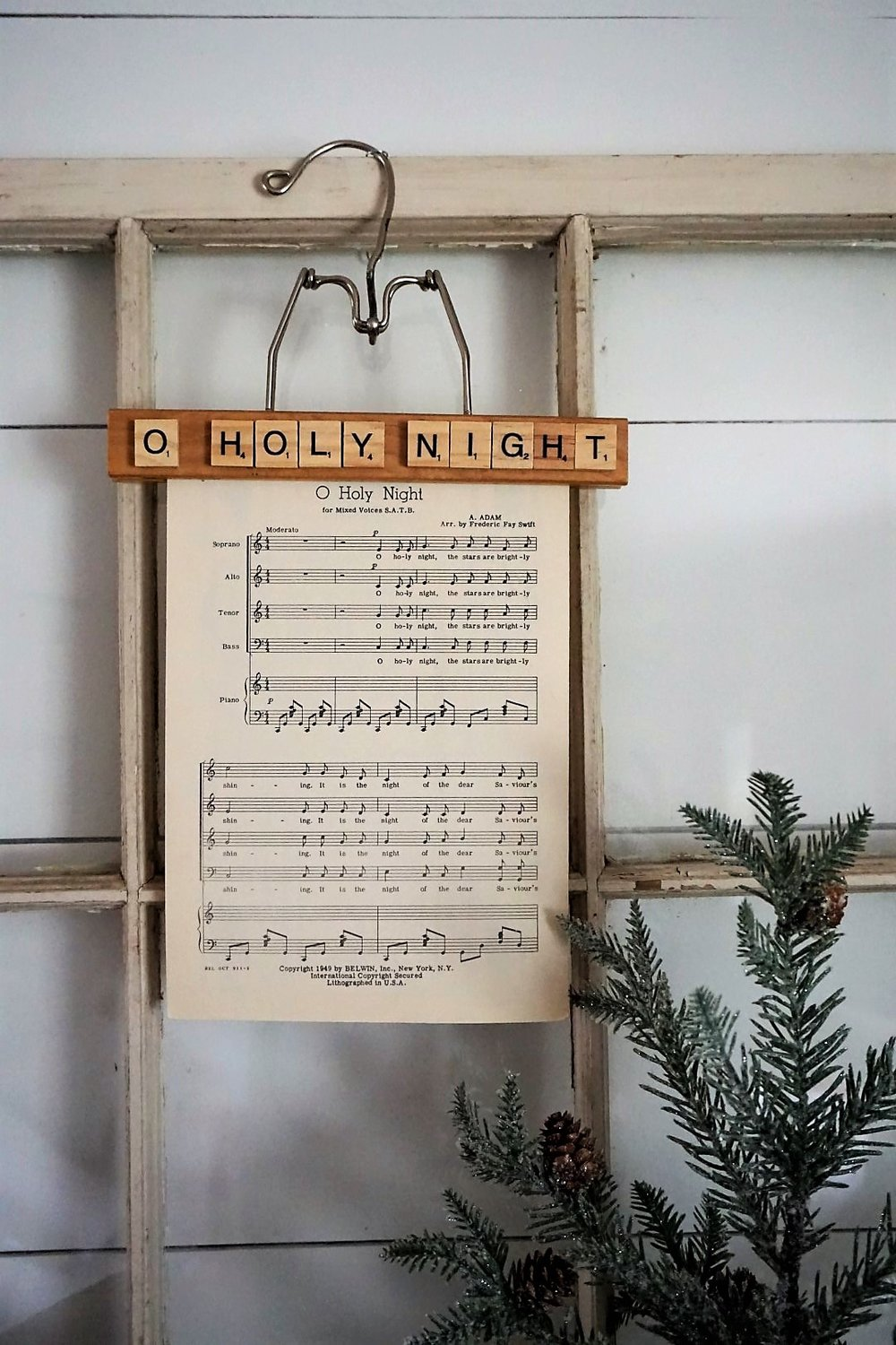Use vintage sheet music and an old wooden hanger to create stylist Christmas decor. Click here for the tutorial and supply list! #christmasdiy #christmascrafts #sheetmusic #christmasdecorations #christmasdecor #diychristmasdecor