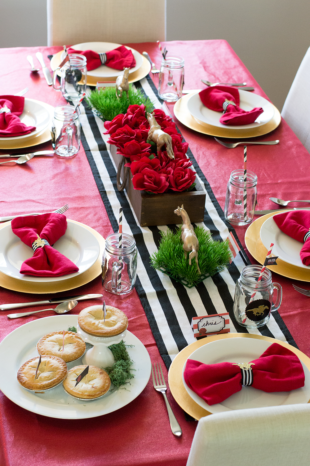 Red tablecloth with black and white striped runner and a rose centerpiece make the perfect Kentucky Derby dinner party setting.
