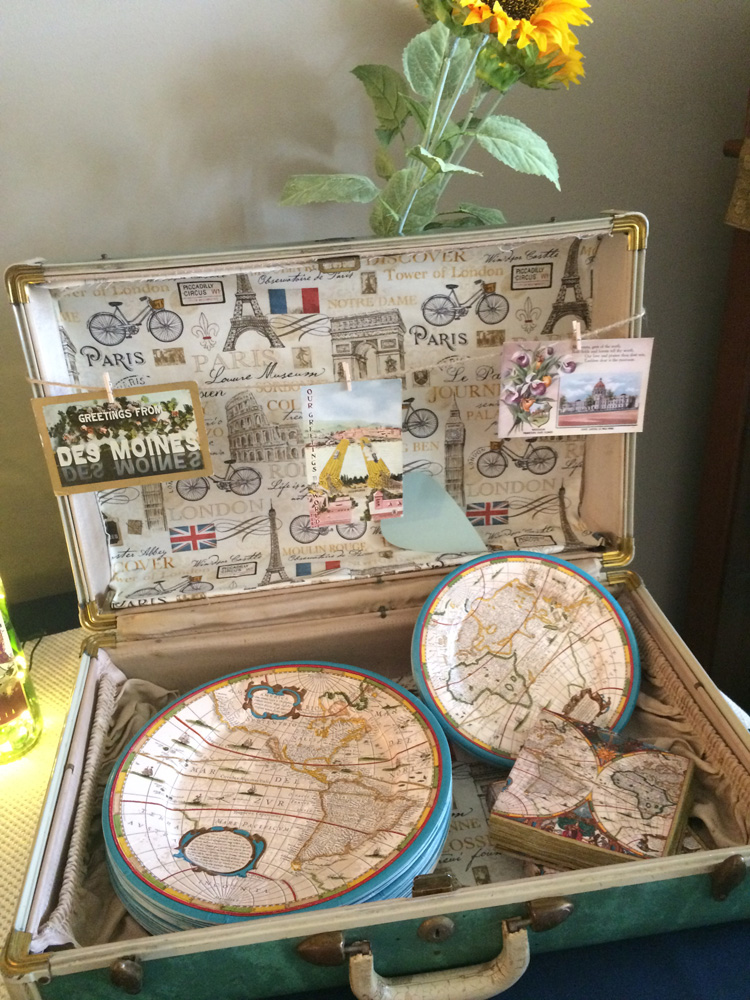 Vintage suitcase with globe plates and napkins for a travel themed bridal shower.