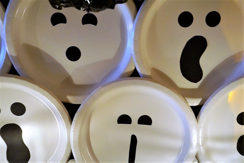 DIY Halloween ghost backdrop made with white plates and black cardstock.