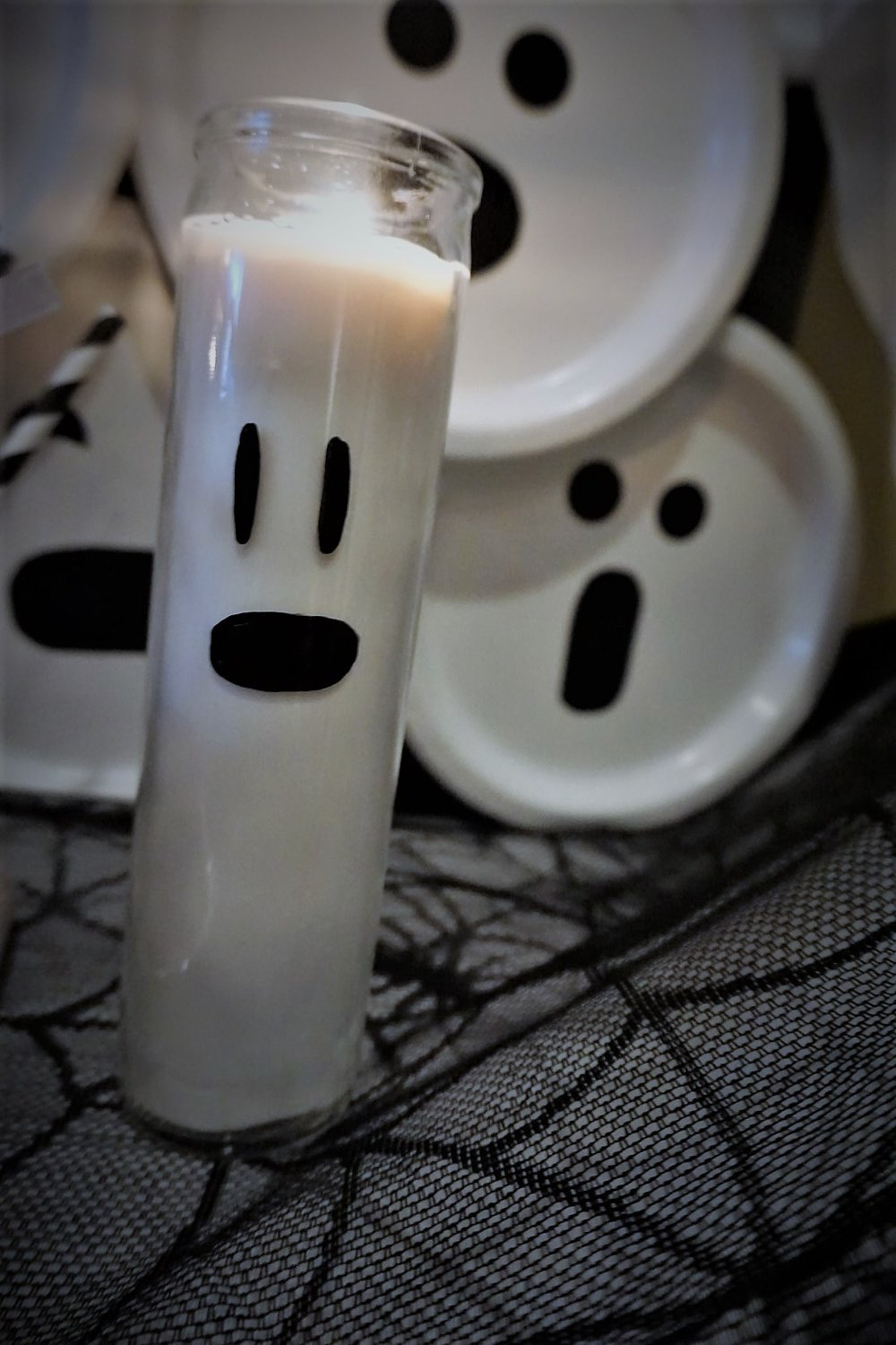 DIY ghost candles with dollar store candles and sharpies.