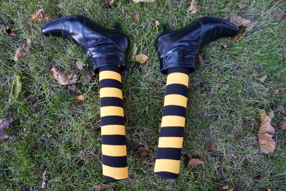 DIY witch legs are made easy with thrift store boots, pool noodles, and striped socks. #diyhalloween #halloweencrafts #halloweendiy #witchlegs
