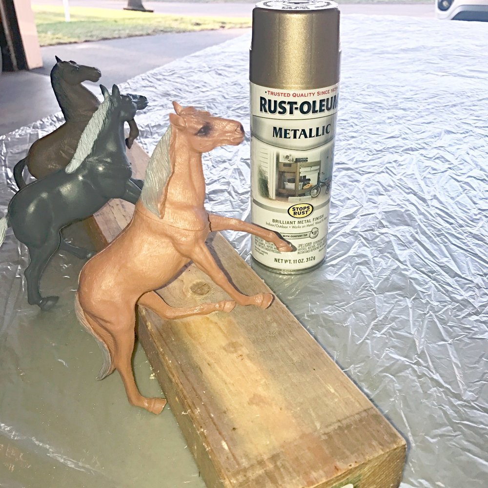 Dollar store plastic toy horses reading to be spray painted with gold spray paint.