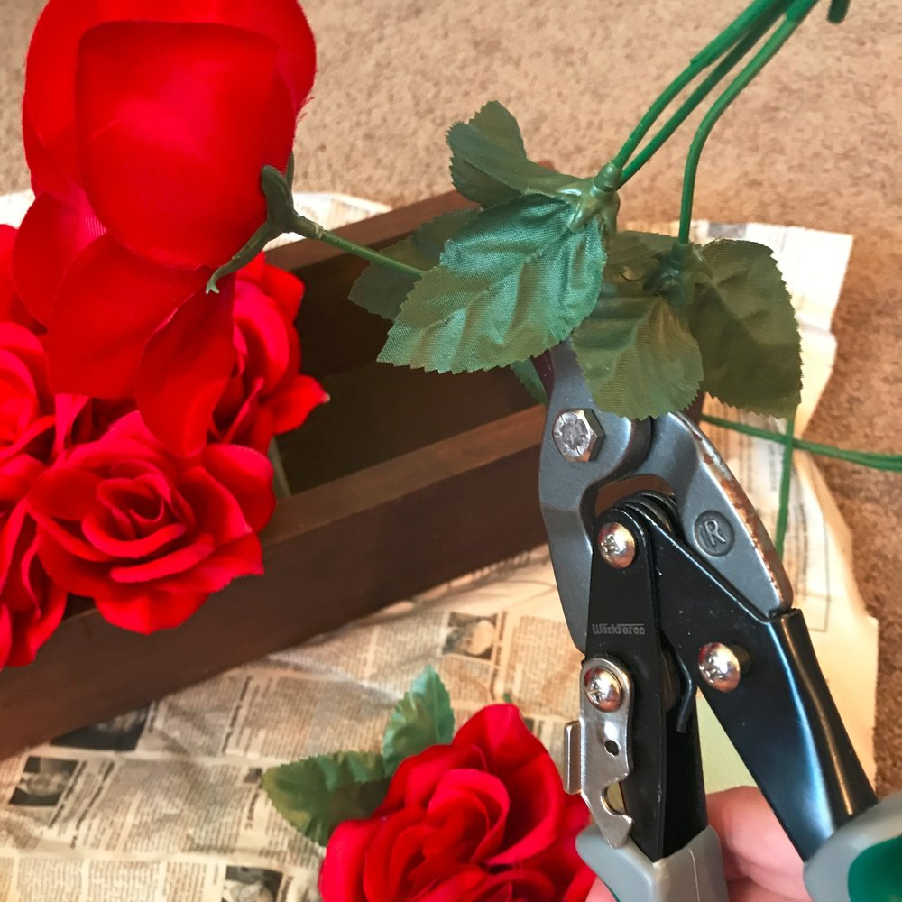 Use a wire cutter to trim down dollar store faux roses to make a centerpiece.